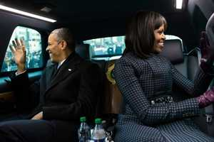 President Barack Obama and First Lady Michelle Obama wave to people as they ride in the inaugural parade in Washington, D.C., Jan. 21, 2013.