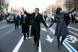 President Barack Obama and First Lady Michelle Obama wave to the crowd as they walk in the inaugural parade along Pennsylvania Avenue in Washington, D.C., Jan. 21, 2013.