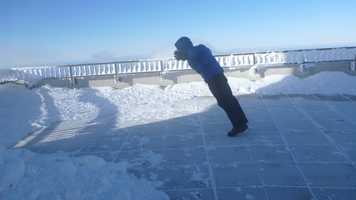 """Weather Observer and Educational Specialist Brian Fitzgerald attempts to make his way to the railing to make a weather observation. Winds are sustained just under hurricane force in this picture. The combination of these winds and temperature in the mid negative twenties allows for a wind chill of -74 degrees.  (""""The Mount Washington Observatory"""" / www.MountWashington.org)"""