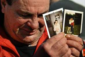 """Steven Ayer, of West Warwick, R.I., displays photographs of his daughter Tina, 33, near the site of """"The Station"""" nightclub, Feb. 21, 2003."""