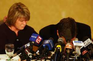 Jeff Dederian, right, co-owner of The Station nightclub, cries with his head in his hands as he reads a statement to the media and his wife Linda Derderian, left, looks on.