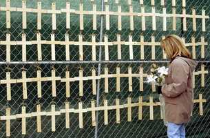Maggie Cardinale of Narragansett, R.I., pauses by a grouping of wooden crosses hanging on a fence enclosing the burnt wreckage of The Station nightclub in West Warwick, R.I., representing those killed from the fire. Cardinale brought lilies in remembrance of her friend, Lisa D'Andrea, who was among the dead.