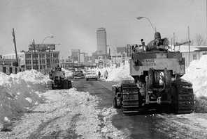Two members of the U.S. Army 27th Engineers from Fort Bragg, N.C. move their bulldozers slowly toward downtown Boston as the city began to remove the record snowfall from the streets, seen in this Feb. 11, 1978 file photo.