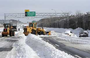 Payloaders clear snow from the Long Island Expressway just west of exit 59 Ocean Ave where several cars are abandoned after a snow storm on Saturday, Feb. 9, 31, 2013, in Ronkonkoma , N.Y.