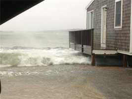 Water gushing over a seawall and under a house in Scituate
