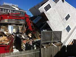 Heavy equipment operators tear down remnants of Plum Island homes.