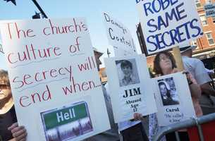 July 30, 2003: Protesters hold signs outside the Cathedral of the Holy Cross in Boston, prior to the installation of Bishop Sean O'Malley as Archbishop of the Boston Archdiocese.