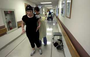 In this Wednesday, July 11, 2012 photo, Meg Theriault works with physical therapist Heather Meunier to practice walking at the Spaulding Rehabilitation Hospital in Boston.