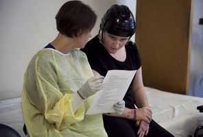 In this Wednesday, July 11, 2012 photo Meg Theriault reviews a list of exercises while working with physical therapist Heather Meunier, left, at the Spaulding Rehabilitation Hospital, in Boston. At this point in her recovery, Meg's mind wouldn't work the way she wanted.