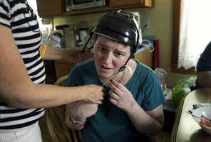 In this Thursday, Aug. 2, 2012 photo, Meg Theriault is helped with a helmet by her mother, Deb Theriault.  At this point in her recovery, Psychiatrist Seth Herman said Meg's memory and mobility had improved a lot, but might never be what they once were. Due to the frontal lobe injury, she had trouble with insight, including recognizing her shortcomings.