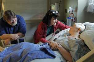 When Meg had pictured coming home to Salisbury, Mass., she expected a trip from the airport, not the hospital. In this Tuesday, Sept. 4, 2012 photo Meg Theriault, right, speaks with her parents Deb, center, and father Todd, left, following surgery to install a plastic plate in Meg's skull at Massachusetts General Hospital, in Boston.