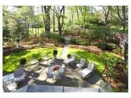 The home is set on nearly an acre of lush estate like grounds with stone walls & patios