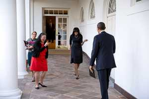 President Barack Obama watches as First Lady Michelle Obama playfully greets him on the Colonnade of the White House, Feb. 12, 2013. Tina Tchen, Chief of Staff to the First Lady, and Personal Aide Kristin Jones, left, accompany Mrs. Obama.