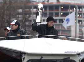 New England Patriots Tom Brady, MVP of Super Bowl XXXVIII, holds up the Super Bowl trophy as he rides in a parade celebrating the teams victory Tuesday, Feb 3, 2004 in Boston.