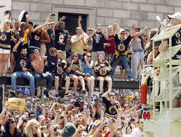 Boston Bruins fans cheer from on top of a bus stop in Copley Square as a duck boat carrying Bruins players goes by during a parade honoring NHL hockey's Stanley Cup Champions Saturday, June 18, 2011 in Boston.