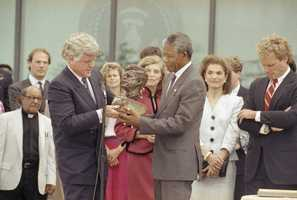 Nelson Mandela receives a bust of the late president John F. Kennedy from the president's brother Sen. Edward Kennedy, left, during a ceremony at the John F. Kennedy library, June 23, 1990. At far right is Jacqueline Kennedy Onassis. Eunice Shriver, in red dress, sister of Sen. Kennedy looks on behind Mandela. At right is Joe Kennedy II, son of Robert Kennedy.