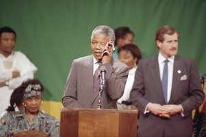Nelson Mandela, deputy president of the African National Congress, wipes his brow in the hot, humid gymnasium of the Madison Park High School in the Roxbury section of Boston, June 23, 1990. An exuberant crowd packed the gymnasium for Mandela's appearance.