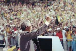 African National Congress deputy president Nelson Mandela gives a raised fist salute to the crowd at the Esplanade in Boston, June 23, 1990, where over 200,000 people gathered to see Mandela.