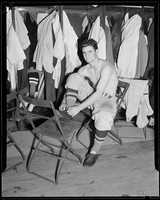 Boston Red Sox Bobby Doerr tying his shoe while sitting in front of his locker at the ballpark in 1937.