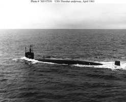 Port broadside view, taken while the submarine was underway with water surging over her bow, 30 April 1961.