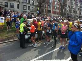 Runners are stopped on the course after the explosions.