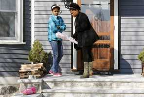 Two women place flowers on the doorstep of the Richard house in the Dorchester neighborhood of Boston, Tuesday, April 16, 2013. Martin Richard, 8, was killed in the Mondays bombings at the finish line of the Boston Marathon. The boy's mother, Denise, and 6-year-old sister, Jane, were badly injured.