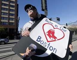 Detroit Tigers' fan Tab Waterman, of Portland, Ore., holds a sign in honor of the victims of the Monday bombings at the Boston Marathon as he stands outside the Seattle Mariners' ballpark before a baseball game against the Tigers in Seattle.