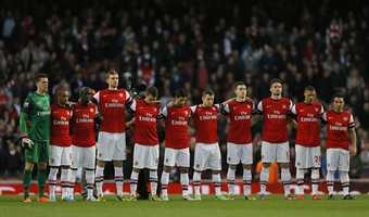 Arsenal's players observe a minute silence for victims of the Boston marathon bombings in the United States, ahead of the English Premier League soccer match between Arsenal and Everton at the Emirates Stadium in London