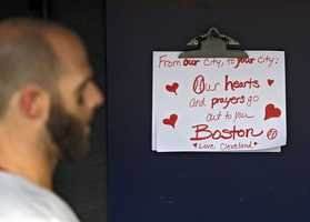 Boston Red Sox's Dustin Pedroia walks past a condolence sign in the dugout before a baseball game against the Cleveland Indians in Cleveland.