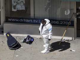 A man in a haz-mat suit investigates the scene near the first bombing on Boylston Street in Boston Tuesday.