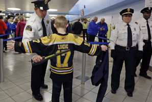 A young Boston Bruins fan raises his arms to be checked on the way into TD Garden prior to a Bruins NHL hockey game