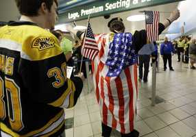 A fan wearing a United States flag raises his arms to be checked on the way into TD Garden