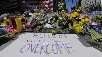 Flowers and signs adorn a barrier at Boylston Street near the of finish line of Monday's Boston Marathon explosions.