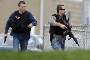 Police run with their weapons drawn as they conduct a search for a suspect in the Boston Marathon bombings, Friday, April 19, 2013, in Watertown, Mass.