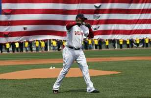 Boston Red Sox's David Ortiz pumps his fist in front of an Amarican flag and a line of Boston Marathon volunteers, background, after addressing the crowd before a baseball game between the Boston Red Sox and the Kansas City Royals in Boston, Saturday, April 20, 2013.