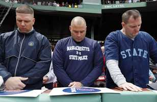 Three members of the Massachusetts State Police bow their head during a moment of silence before a baseball game between the Red Sox and the Kansas City Royals in Boston, Saturday, April 20, 2013.