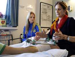 Beth Roche, right, whose left leg was severely injured by one of the bombs that exploded near the Boston Marathon finish line, sits on her bed with her daughter Rebecca Roche, left, at Spaulding Rehabilitation Hospital in Boston.