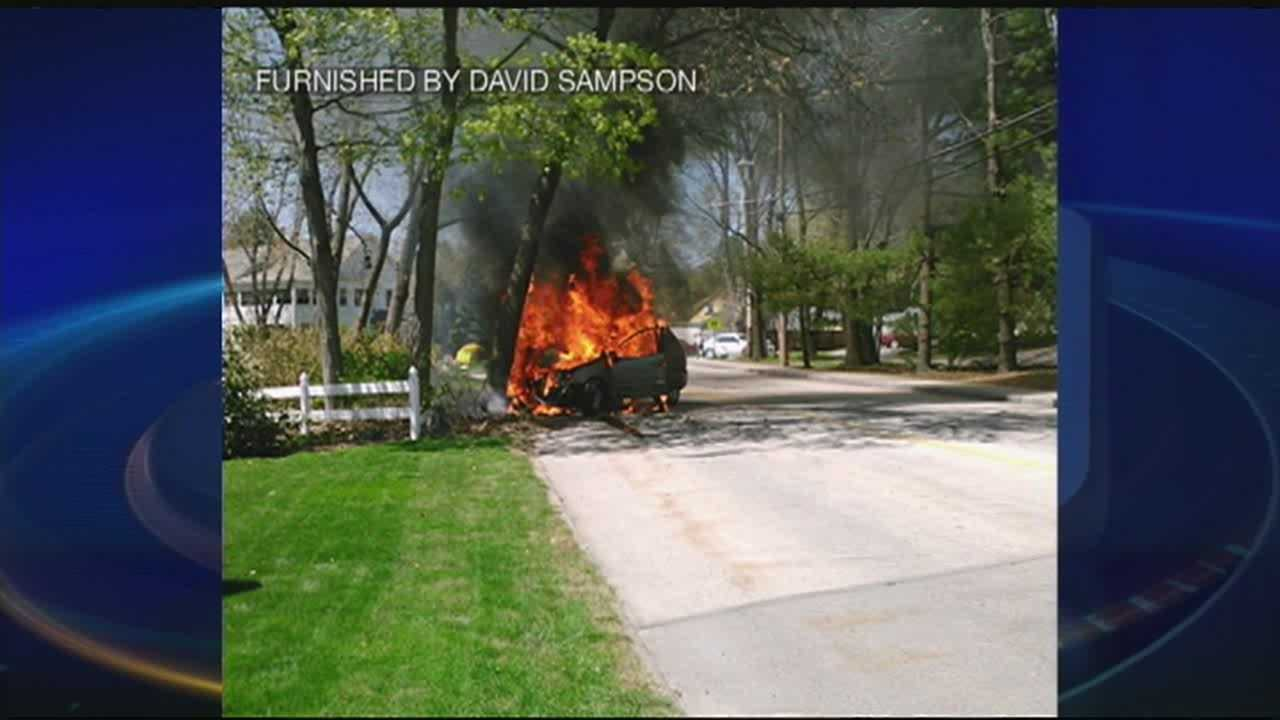 Bystanders pull woman from burning car