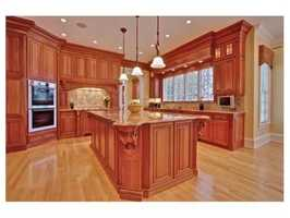 The kitchen has floor-to-ceiling cherry cabinetry.