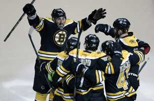 Boston Bruins defenseman Adam McQuaid, front center, celebrates his goal against the Pittsburgh Penguins with teammates including left wing Brad Marchand, left, during the third period of Game 4 in the Eastern Conference finals of the NHL hockey Stanley Cup playoffs in Boston, Friday, June 7, 2013.