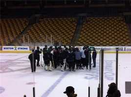 The coach talks to the team one last time on the ice before they are greeted by fans.