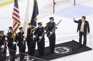 Singer Rene Rancourt, right, gestures toward a Watertown Police Honor Guard, left, on the ice before a NHL hockey game between the Boston Bruins and the Florida Panthers at the TD Garden in Boston, Sunday, April 21, 2013.