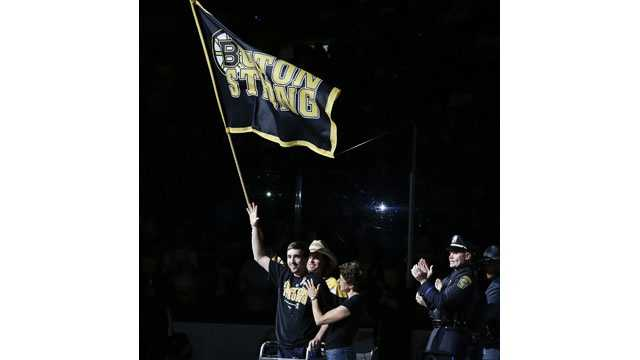Jeff Bauman walks, waves flag