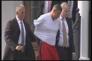 Hernandez was wearing a white V-neck T-shirt, with his arms inside the shirt and behind his back as he was led from his North Attleborough home Wednesday morning.