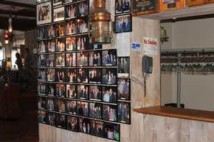 Dozens of photographs of celebrities covered the wall next to the coatroom