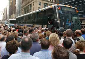 Commuters crowd around to board a mid-town Manhattan bus to White Plains after a power outage in New York knocked out train service, Thursday, Aug. 14, 2003.