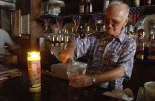 Dr. Bill makes a drink by candle light, Friday, Aug. 15, 2003, at a bar in the Hell's Kitchen neighborhood of New York which remained without power after a massive blackout which affected parts of the Northeast, Midwest and Canada.