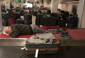 In a Friday, Aug. 15, 2003 file photo a stranded traveler sleeps in the baggage claim area at John F. Kennedy International Airport in New York.