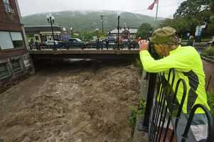 The torrential rains from the storm caused flash flooding that started Sunday, Aug. 28, 2011. Mel Martin joins a crowd watching the raging Whetstone Brook surge over the falls in downtown Brattleboro, Vt.