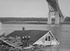 Sailors stand on what remained of their guard house under the Bourne Bridge.